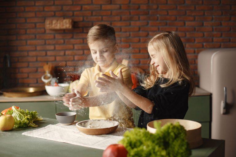 Ernährungsberatung, Kinder in der Küche spielen mit Mehl